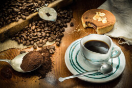 Food photography, foodie photo of table with coffee and cake with ground coffee in the foreground